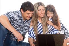 Familia usando una computadora portátil Fotografía de archivo libre de regalías