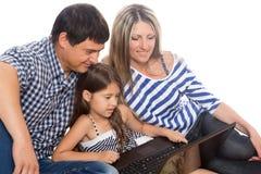 Familia usando una computadora portátil Imagen de archivo libre de regalías
