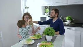 Familia vegetariana, padres felices con el niño que come la comida sabrosa que se sienta en la tabla en cocina metrajes