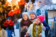 Familia vigorosa de tres en el mercado de la Navidad Fotografía de archivo libre de regalías