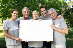 Familia voluntaria feliz que lleva a cabo un espacio en blanco Fotografía de archivo