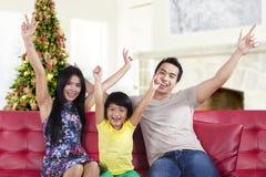 Familia y árbol de navidad emocionados en casa imagen de archivo