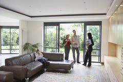 Familia y agente de la propiedad inmobiliaria At New Property imagen de archivo libre de regalías