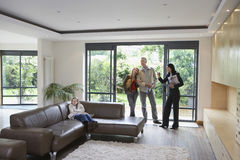 Familia y agente de la propiedad inmobiliaria Observing New Property Foto de archivo libre de regalías
