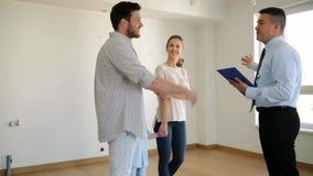 Familia y agente inmobiliario felices en la nueva casa o el apartamento almacen de metraje de vídeo