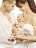 Familia y bebé recién nacido, padres que se consideran recién nacidos Fotos de archivo libres de regalías