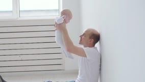 Familia y concepto de los niños El padre joven feliz detiene a su hija recién nacida almacen de video