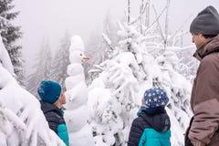 Familia y muñeco de nieve en bosque de la nieve del invierno imagenes de archivo