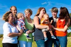 Familia y multigeneración - diversión en prado Fotografía de archivo