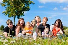Familia y multigeneración - diversión en prado en suma Imágenes de archivo libres de regalías