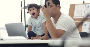 Familia y niña modernas asiáticas, mientras que el papá trabaja con el cuaderno metrajes