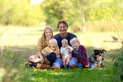 Familia y perro casero jovenes felices afuera Fotos de archivo