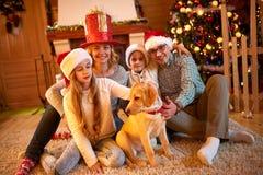 Familia y perro que se sientan por el árbol de navidad Imágenes de archivo libres de regalías