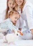 Familia y un pequeño conejo blanco Fotos de archivo libres de regalías