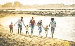 Familias multirraciales felices que corren junto en la playa en la puesta del sol Foto de archivo libre de regalías