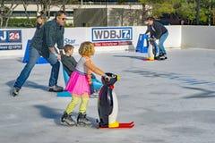 Familias que aprenden al patinaje de hielo fotografía de archivo