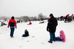 Familias que disfrutan de sledding en el tiempo nevoso en el parlamento hola fotografía de archivo libre de regalías