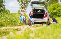 Familie ändert den Reifen des Autos Stockbilder