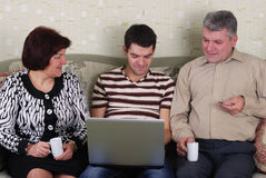 Familie. A men and a women and a young guy on the couch with a laptop Royalty Free Stock Photo