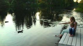 Familie aan het meer zitting en het letten op werk stock videobeelden