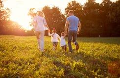 Familie in aard samen, achtermening Royalty-vrije Stock Afbeeldingen