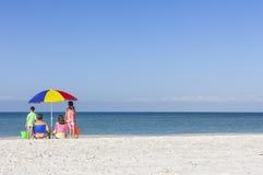 Familie allein auf Strand mit Regenschirm Stockbilder