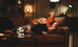 Familie alvorens de naar bed te gaan moeder aan haar boek van de kindzoon dichtbij een lamp in de avond leest royalty-vrije stock foto