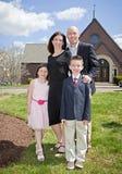 Familie außerhalb der Kirche Stockbild