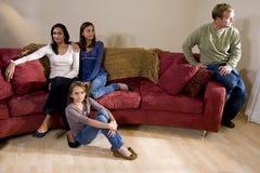 Familie auf Couch mit dem Vater, der auseinander sitzt lizenzfreies stockbild