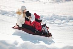 Familie auf dem Schlitten, der sich abwärts schnell bewegt stockfotografie