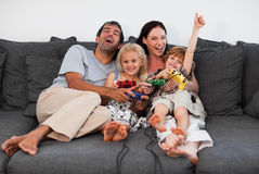 Familie auf dem Sofa, das Videospiele spielt Lizenzfreie Stockfotos