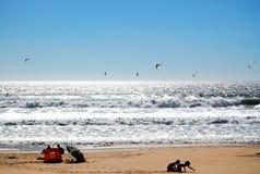 Familie auf dem Strand mit Drachen Lizenzfreie Stockbilder