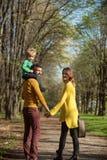 Familie auf dem Wandern des Abenteuers durch Waldvater geben Kinderdoppelpolfahrt auf Wanderweg Sein ein wirkliches Vergnügen lizenzfreie stockbilder