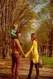 Familie auf dem Wandern des Abenteuers durch Waldvater geben Kinderdoppelpolfahrt auf Wanderweg Sein ein wirkliches Vergnügen lizenzfreies stockfoto