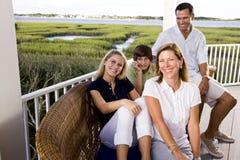 Familie auf den Ferien, die zusammen auf Terrasse sitzen Stockbild