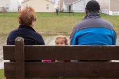 Familie auf der Bank, die in den verschiedenen Richtungen schaut Lizenzfreies Stockbild