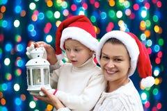 Familie auf einem Hintergrund von Weihnachtslichtern Stockfotos