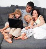 Familie auf einem Sofa mit Laptop Stockbild