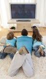 Familie auf Fußboden in überwachendem Fernsehen des Wohnzimmers lizenzfreie stockfotografie