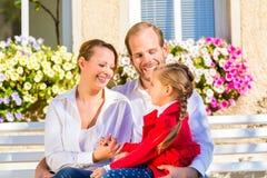 Familie auf Gartenbank vor Haus Stockbild