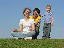 Familie auf Gras sitzen stockfotos
