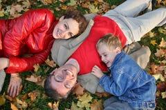 Familie auf Herbstblättern Stockfotografie