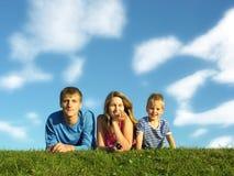 Familie auf Kraut unter blauem Himmel Lizenzfreie Stockfotos