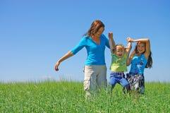 Familie auf Kraut unter blauem Himmel Stockfoto