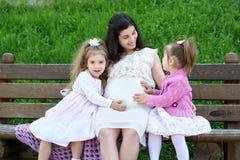 Familie auf, schwangerer Frau im Freien mit Kind im Stadtpark, Sommersaison, grünem Gras und Bäumen Lizenzfreies Stockbild
