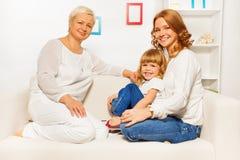 Familie auf Sofa mit Muttermädchen und -oma Lizenzfreies Stockbild