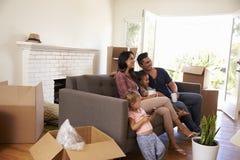 Familie auf Sofa Taking ein Bruch vom Auspacken aufpassenden Fernsehens lizenzfreie stockfotos