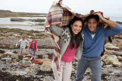 Familie auf Strand mit Decken stockfotografie
