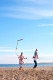 Familie auf Strand mit Drachen Stockbilder