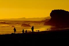 Familie auf Strand am Sonnenuntergang Lizenzfreie Stockfotos